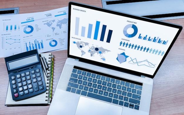 上面図は、会議室のテーブルに計算機と事務処理を備えたディスプレイノートパソコンでの販売概要スライドショープレゼンテーションをモックアップします