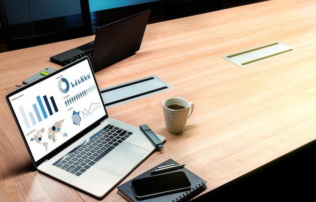 上面図は、会議室のテーブルにコーヒーカップを備えたディスプレイノートパソコンでの販売概要スライドショープレゼンテーションをモックアップします。