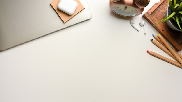 Top view of mock up scene with laptop stationery decorations and copy space on white desk