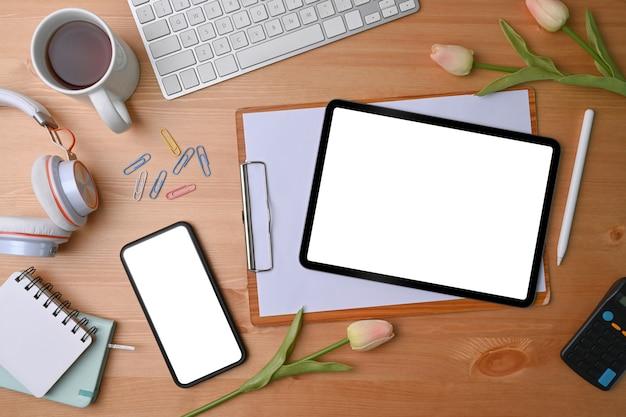 Вид сверху макет смартфона и цифрового планшета с пустым экраном на деревянном столе.