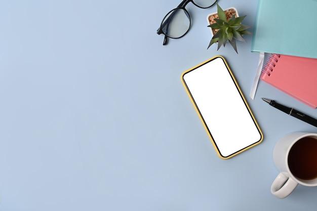 上面図は、青い背景にスマートフォン、メガネ、コーヒーカップ、ノートブックをモックアップします。