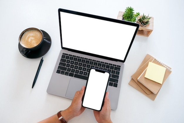 Top view mockup image of hands holding a blank white screen mobile phone and laptop computer on the table in office