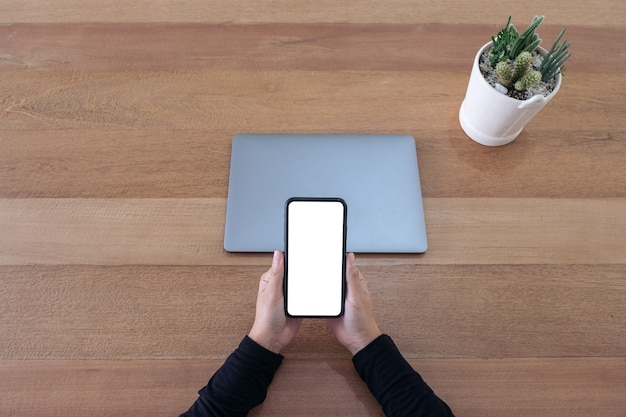 Top view mockup image of a hands holding a blank white screen mobile phone and laptop on wooden table in office