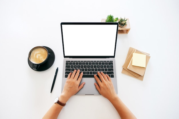 Top view mockup image of hands using and typing on laptop with blank white desktop screen on the table