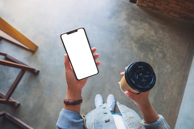 コーヒーカップと空白の白いデスクトップ画面と黒の携帯電話を保持している女性の上面モックアップ画像