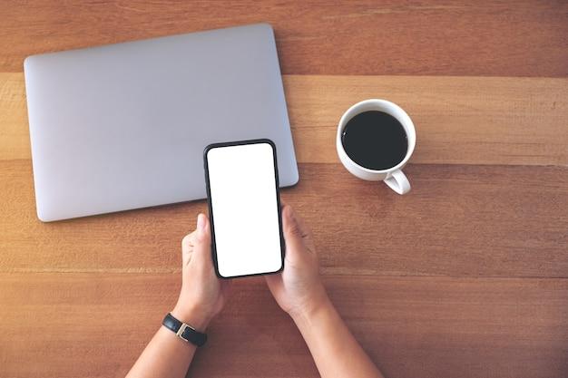 Вид сверху макета изображения женщины, держащей и использующей черный мобильный телефон с пустым белым экраном рабочего стола с чашкой кофе и портативным компьютером на деревянном столе
