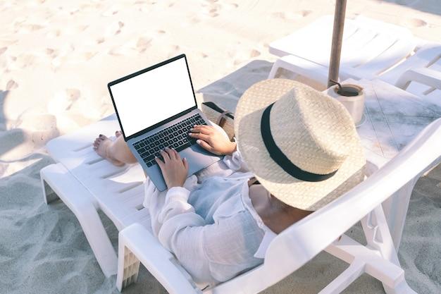 Вид сверху макета женщины, держащей и использующей портативный компьютер с пустым экраном рабочего стола, лежа на шезлонге на пляже