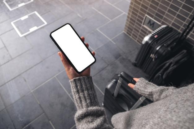 空白のデスクトップ画面で黒い携帯電話を保持している女性の上面モックアップ画像