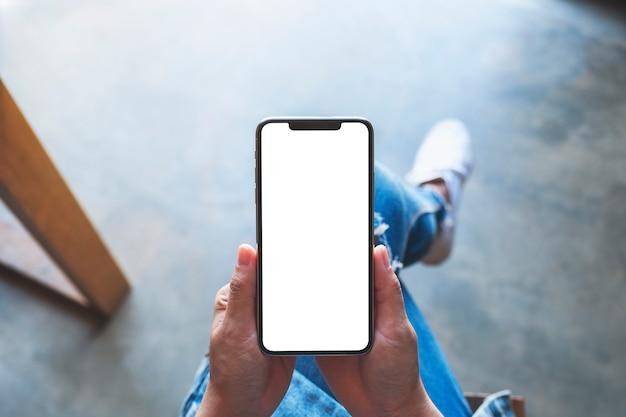 カフェに座っている間空白の白い画面で黒い携帯電話を保持している女性の上面モックアップ画像