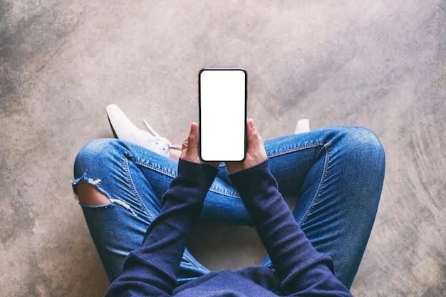 바닥에 앉아 있는 동안 빈 흰색 화면이 있는 검은색 휴대폰을 들고 있는 여성의 상위 뷰 모형 이미지