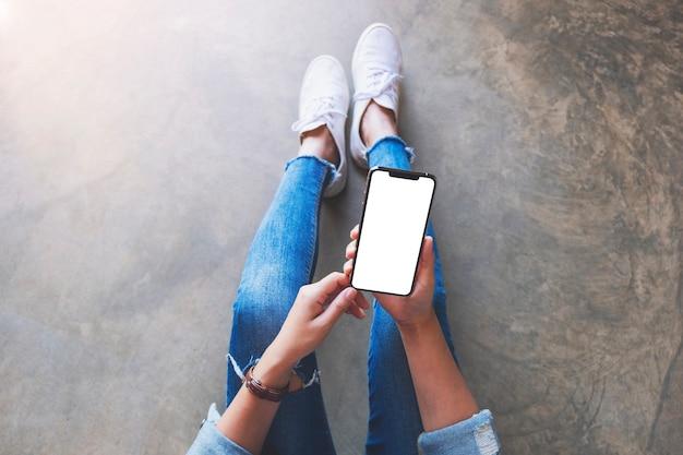 床に座っている間空白の白い画面で黒い携帯電話を保持している女性の上面モックアップ画像