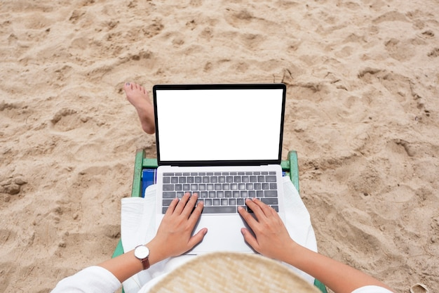 ビーチチェアに横になっている間、空白のデスクトップ画面でラップトップコンピューターを使用して入力している女性の上面モックアップ画像