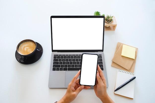 空白の白い画面の携帯電話とラップトップコンピューターをオフィスのテーブルに持っている手の上面モックアップ画像