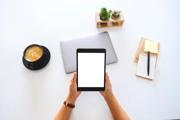 空白の白い画面とラップトップコンピューターがオフィスのテーブルにタブレットを持っている手の上面モックアップ画像