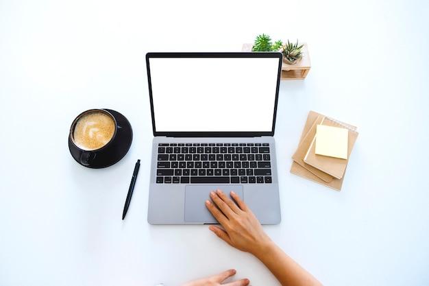 テーブルの上の空白の白いデスクトップ画面でラップトップのタッチパッドを使用して触れている手の上面図のモックアップ画像