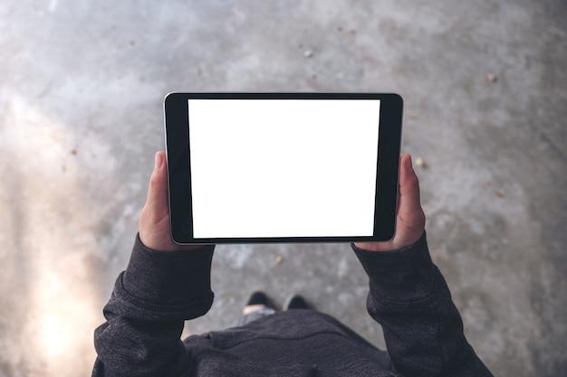 Вид сверху макет изображения руки женщины, держащей и использующей черный планшетный пк с пустым белым экраном рабочего стола по горизонтали, стоя на открытом воздухе