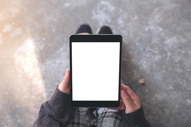 Вид сверху макет изображения руки женщины, держащей и использующей черный планшетный пк с пустым белым экраном рабочего стола, сидя на полу
