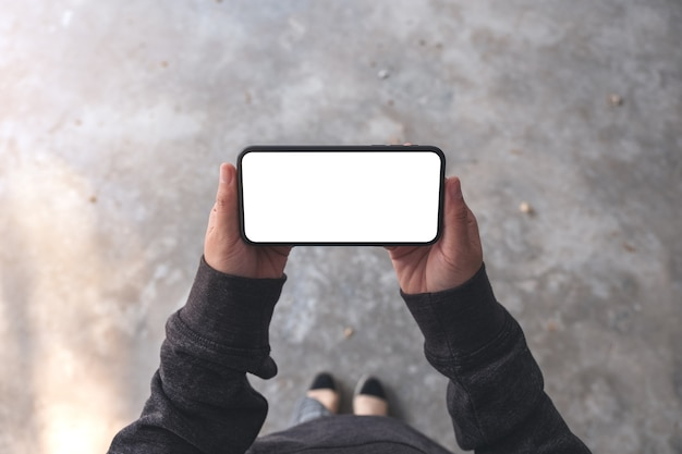 Top view mockup image of a woman holding black mobile phone with blank desktop screen horizontally while standing on concrete floor