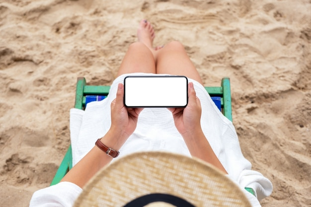 Top view mockup image of a woman holding black mobile phone with blank desktop screen while lying down on a beach chair