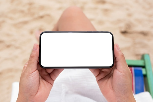 Top view mockup image of a woman holding black mobile phone with blank desktop screen while sitting on a beach chair
