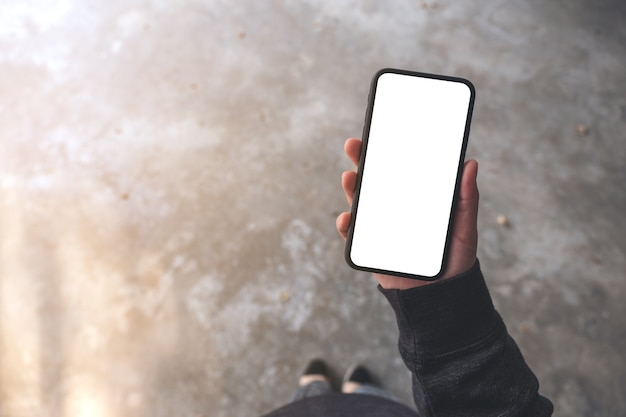 Top view mockup image of a woman holding black mobile phone with blank desktop screen while standing on concrete floor