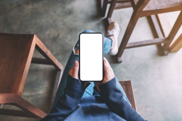 Top view mockup image of a woman holding black mobile phone with blank white screen while sitting in cafe