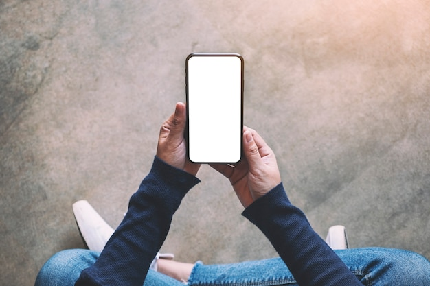 Top view mockup image of a woman holding black mobile phone with blank white screen while sitting on the floor