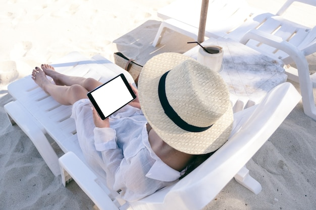Top view mockup image of a woman holding a black tablet pc with blank desktop screen while laying down on beach chair on the beach