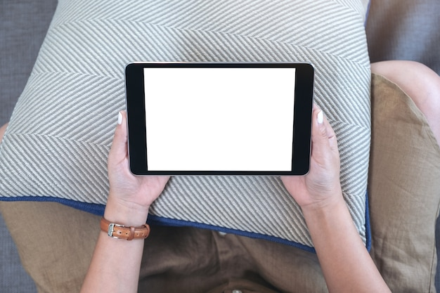 Top view mockup image of a woman holding black tablet pc with blank white desktop screen horizontally while sitting in living room with feeling relaxed