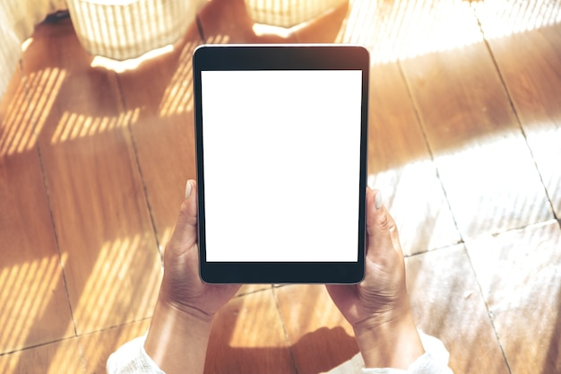 Top view mockup image of a woman holding black tablet pc with blank white desktop screen  while laying down on the wooden floor