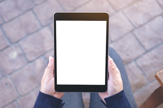 Top view mockup image of a woman holding black tablet pc with blank white screen while sitting in the outdoors