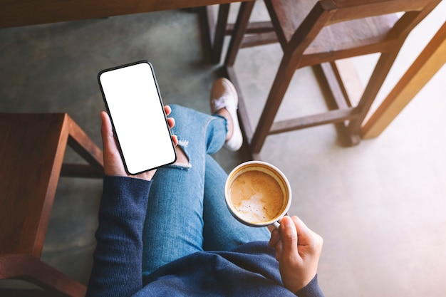 Top view mockup image of a woman holding white mobile phone with blank screen while drinking coffee