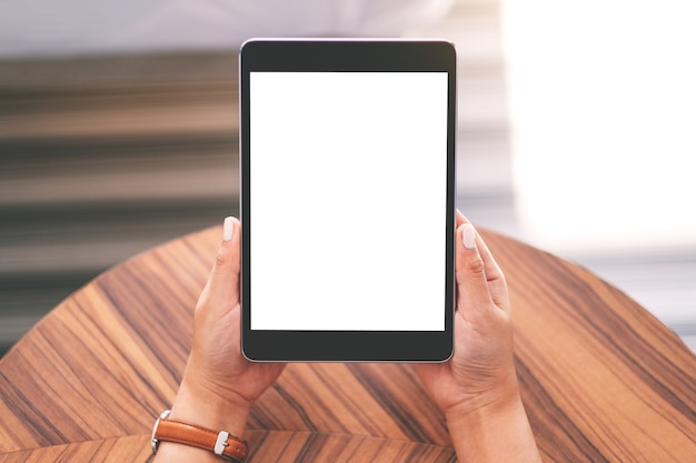 Top view mockup image of a woman sitting and holding black tablet pc with blank white desktop screen on wooden table