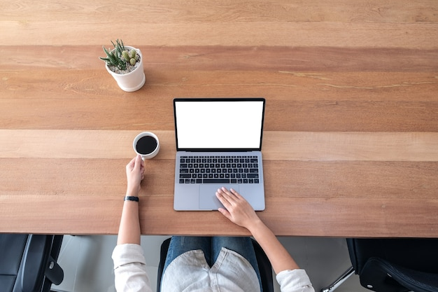 Top view mockup image of a woman using and touching on laptop touchpad with blank white desktop screen while drinking coffee on wooden table in office