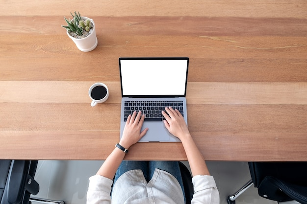Top view mockup image of a woman using and typing on laptop with blank white desktop screen on wooden table in office