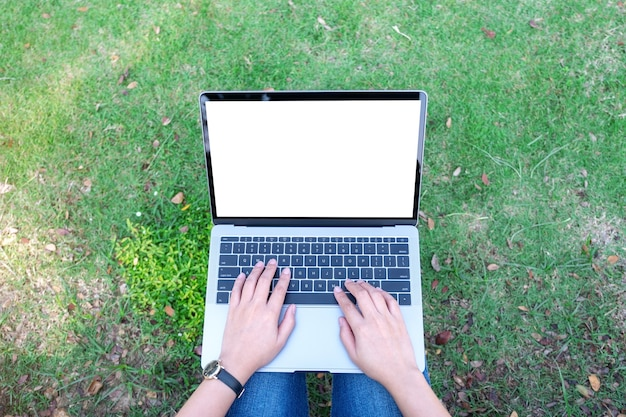 Top view mockup image of a woman using and typing on laptop with blank white screen , sitting in the outdoors with nature background