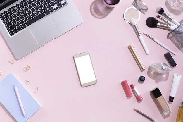 Top view of mockup of mobile phone with white blank copy space screen in female hand. flat lay women workspace with laptop, decorative cosmetic set, stationery and flowers, hard light