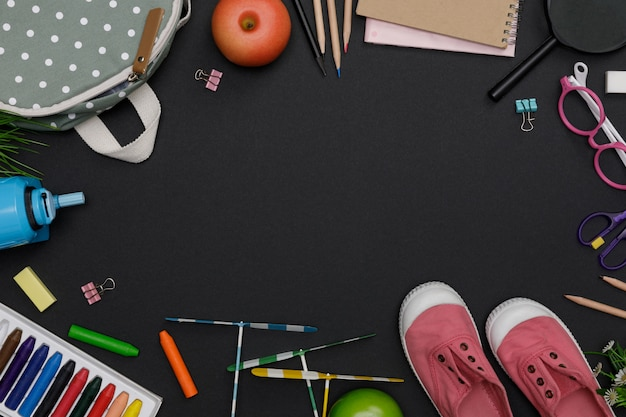 バックパック、学生の本、靴、カラフルなクレヨン、眼鏡、黒板背景、教育の概念と学校に戻って空のスペースで教育のアクセサリーのトップビューモックアップ