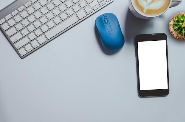 Вид сверху макет смартфона, клавиатуры, кофейной кружки и кактуса на фоне. место для копирования
