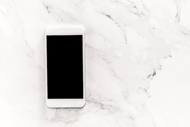Top view of mockup smartphone with blank screens on white marble background.