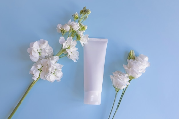 Top view of mockup of white squeeze bottle plastic tube and white flowers on pale blue background.