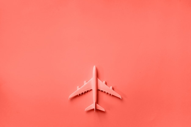 Top view of model plane, airplane toy on pink pastel background