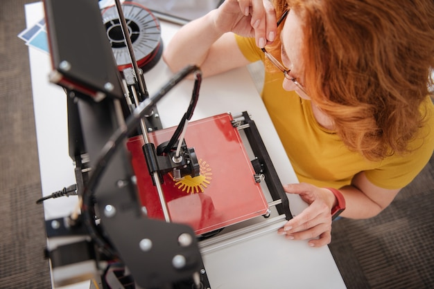 Top view of a modern 3d printer creating a three dimensional object while being used by professional designers