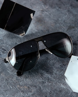 A top view modern black sunglasses on the grey background isolated vision spectacles elegance