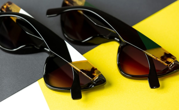 A top view modern black sunglasses pair on the yellow-black background isolated vision spectacles elegance