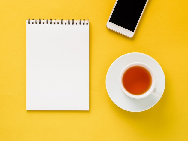 Top view of modern bright yellow office desktop  blank notepad, cup of tea, smartphone