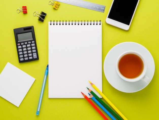 Top view of modern bright yellow office desktop with blank notepad, cup of tea and supplies.