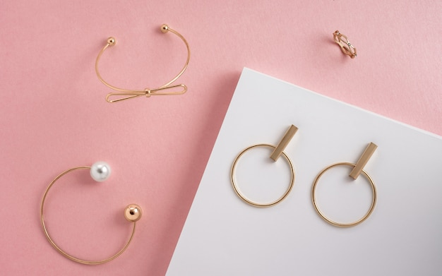 Top view of modern golden girl accessories bracelets and earrings on pink and white surface