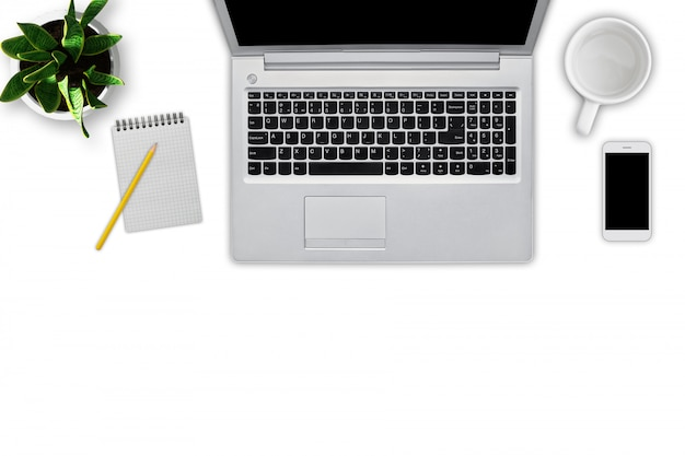 Top view of modern laptop computer, notebook with pencil, empty cup, cell phone and flowerpot isolated on white. workplace of business person. up-to-date gadgets. technology concept