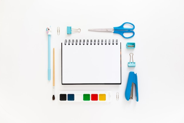 Top view of modern white blue office desktop with school supplies and stationery on table around empty space for text. back to school concept flat lay with mockup